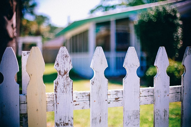 Photo of a white picket fence in front of a house