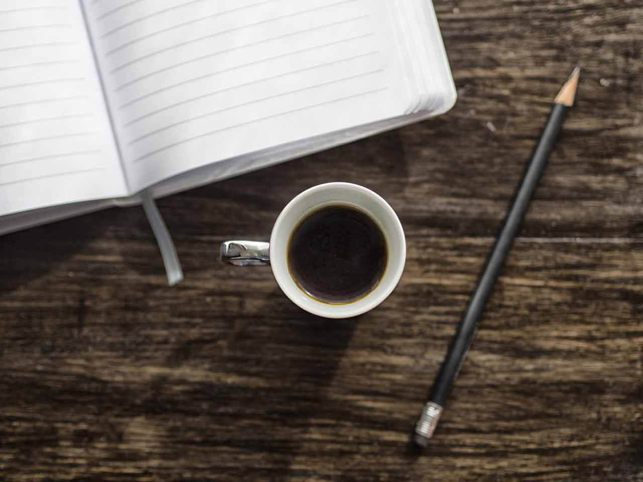 A photo of an empty journal, a cup of coffee, and a pencil.
