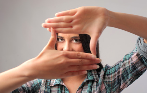 A woman looking through her fingers to see the word in another perspective.