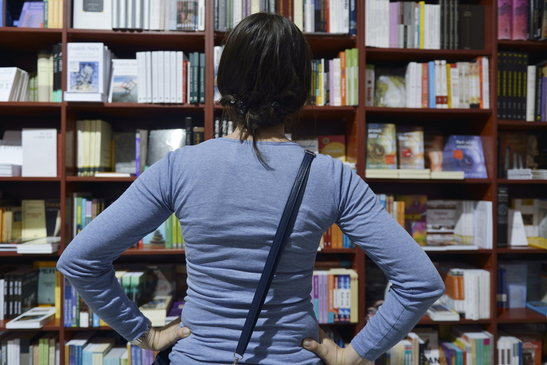 Photo of a Woman Looking at a bookshelf at a bookstore.