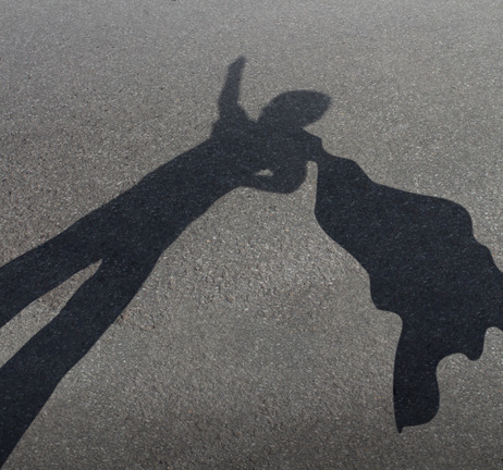 Superhero kid pretending to be a powerful courageous hero with a cape flying in the wind as a fun childhood play symbol for the fertile imagination of a child as a cast shadow on an urban asphalt road.