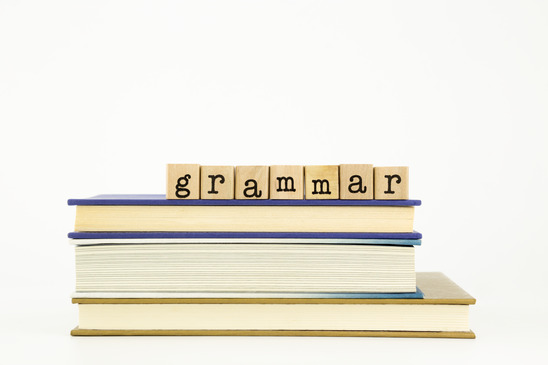 Photo of the word, grammar, spelled out in blocks on top of a pile of books.