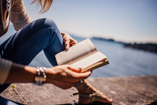 Photo of a girl reading on the beach
