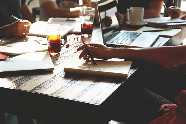 """Image of a group of people writing for the blog post, """"Are Book Clubs & Writing Groups a Waste of Time"""" by Literative.com."""