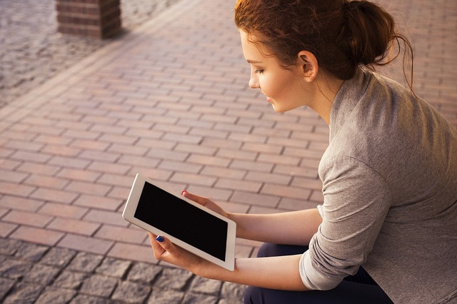 A photo of a woman sitting on a street holding a tablet.